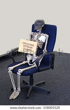 Skeleton holds sign saying should have gotten flu shot - stock photo