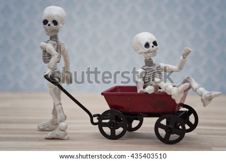 Skeleton kids playing toy wagon with light blue background - stock photo
