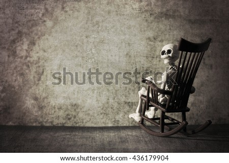 Skeleton looking back while sitting the rocking chair grungy textured - stock photo