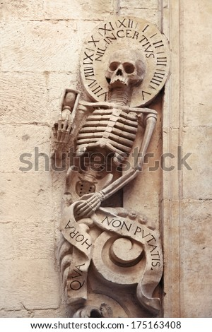 "Skeleton on Church of Purgatory (1747), Bitonto, Italy. He holds a sandglass, the halo with clock cipher,  ""nil incentius (die mortis)"" means ""nothing is as uncertain as the time of death"". - stock photo"