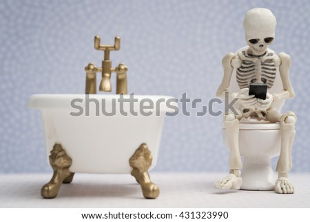Skeleton sitting on water closet and getting busy with his smartphone