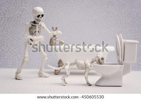 Skeleton watching his skeleton dog drink out of toilet - stock photo