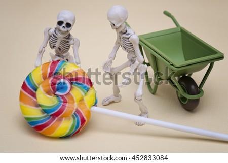 Skeletons hauling lollipop - stock photo
