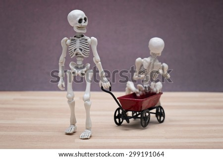 Skeletons playing toy wagon - stock photo