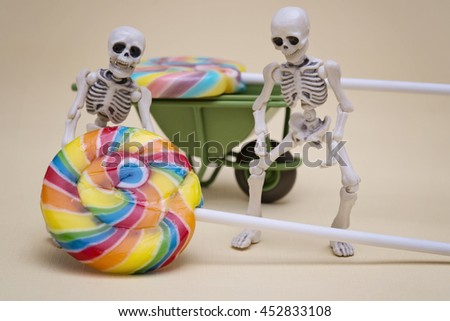 Skeletons try to haul lollipop - stock photo