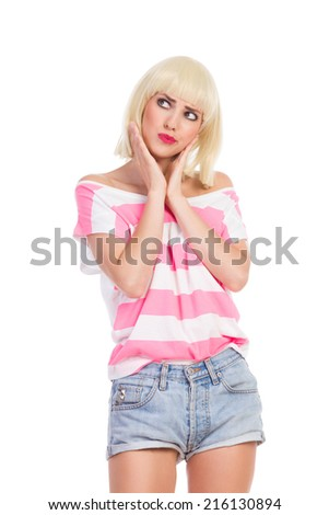 Skeptic woman. Grimacing blonde young woman holding hands on chin and looking away. Three quarter length studio shot isolated on white. - stock photo
