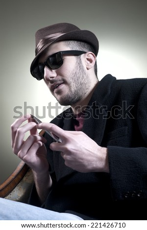 Skeptical guy cleaning finger nails  with knife
