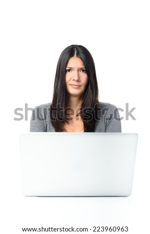Skeptical Long Hair Young Woman Busy with her Laptop while Looking at the Camera, Isolated on White Background.