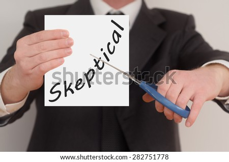 Skeptical, man in suit cutting text on paper with scissors - stock photo