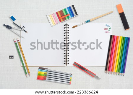 Sketch book and paint tools on table cloth - stock photo