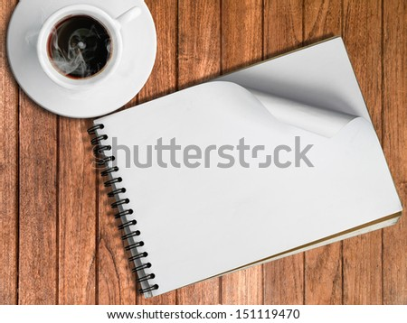 Sketch book and White cup of hot coffee on wood table - stock photo