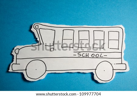 SKETCH made by a child, little School bus draw on a cut out white piece of paper shot on a bright Cyan blue background
