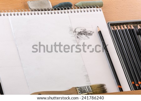 Sketch pad with partially completed image and art equipment on wooden easel.  Shading a dog drawing. - stock photo