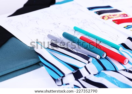 Sketches of clothes and fabric samples on table - stock photo