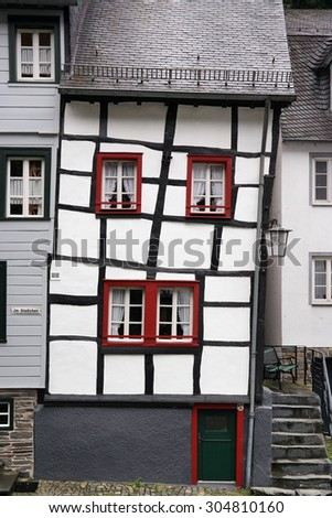Skewed half-timbered house in the historical town center of Monschau a small resort town in the Eifel region of North Rhine-Westphalia, western Germany popular tourist, attraction - stock photo