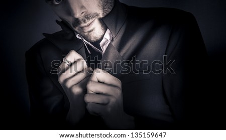 Skewed studio fashion portrait of a rough unshaven young man in elegant formal suit with hand ring accessory