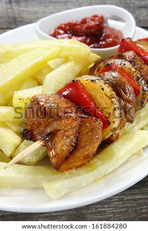 Skewer of pork with french fries
