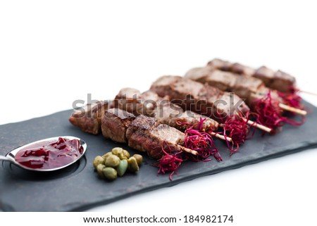 Skewered beef (yakitori) with sauce isolated on white - stock photo