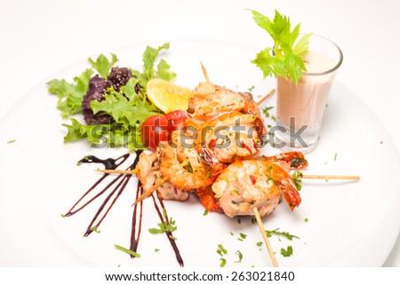 Skewered jumbo shrimps with sauce - stock photo