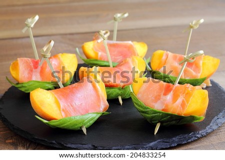 Skewered peaches with prosciutto and basil, original and refreshing appetizer  - stock photo