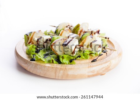 Skewers of cheese, avocado and lettuce on a wooden platter - stock photo