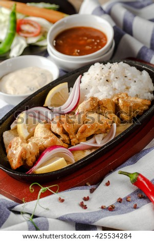 Skewers of grilled chicken in a pan with a side dish of rice - stock photo