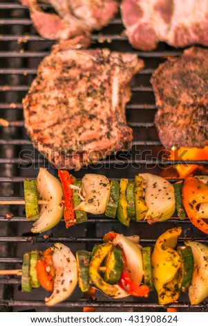 Skewers of meat and vegetables on the grill. Slices of meat with fresh herbs.