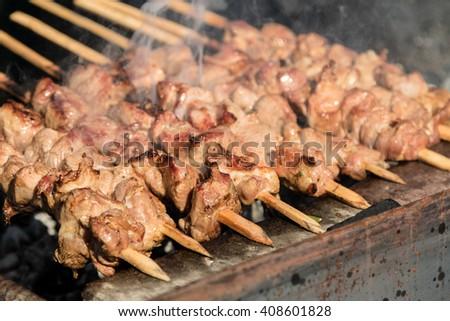 skewers of meat prepares outdoors - stock photo