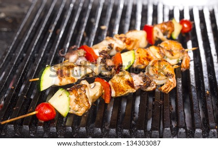 skewers of seafood cooked on the grill