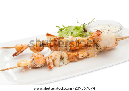 skewers of shrimp with sauce on a white plate - stock photo
