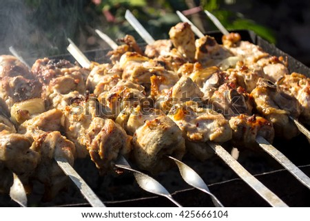 Skewers with a shish kebab on the grill with smoke outdoors - stock photo