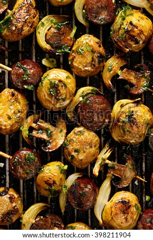 Skewers with potatoes, sausage, mushrooms and onions on grill pan