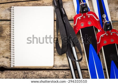 Ski background with empty paper notebook. Ski with poles on old weathered wooden background - stock photo