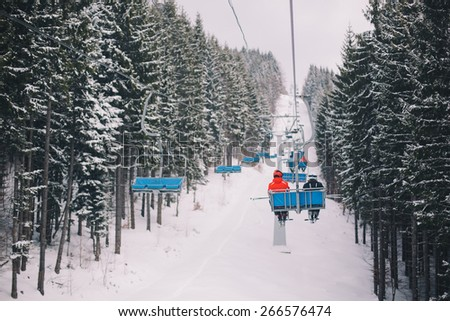 Ski chair lift with skiers in carpathian mountains, Ukraine - stock photo