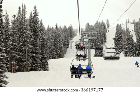 Ski chairlift going up on; trees on both sides of it
