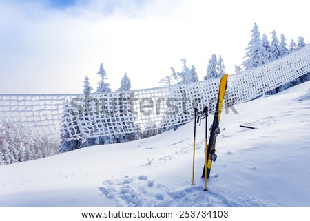 Ski equipment on ski run with pine forest covered in snow seen trough a frozen fence on back in winter season - Poiana Brasov