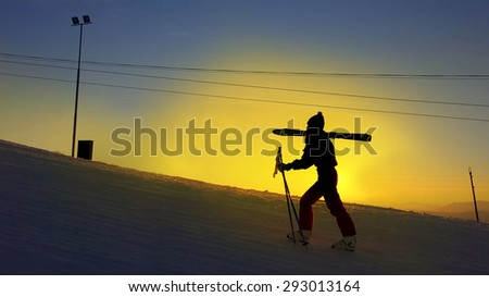 Ski girl climb the slope at winter sunset snow - stock photo
