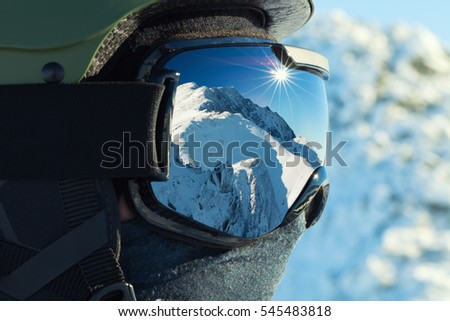 Ski goggles with reflection of snowed mountains in it