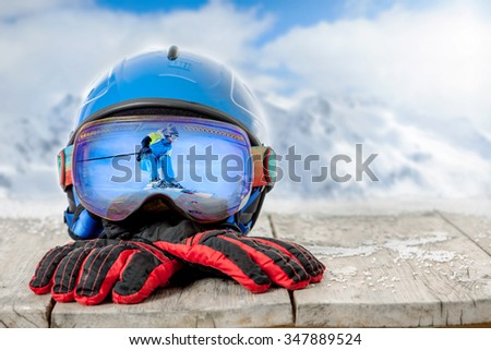 ski helmets and glasses with skier on snow