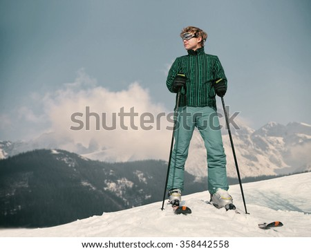 Ski instructor young man on the top of snow hill - stock photo