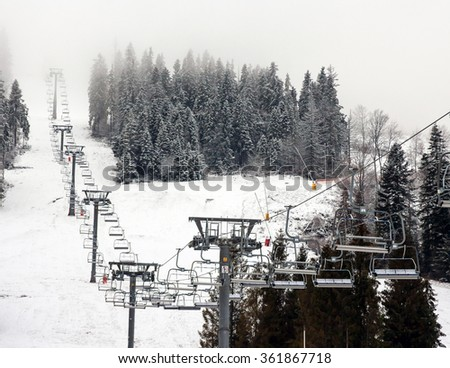Ski lift and snowy spruces on ski resort Play in Carpathian Mountains, Ukraine
