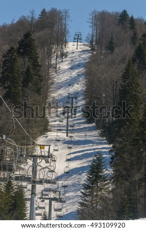 Ski lift at ski resort waiting for new guests, skiers and tourists. High rise on a mountain top with suspicion around.