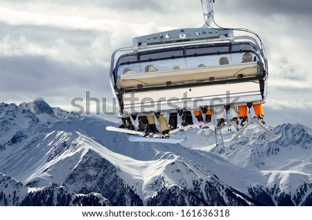 ski lift before mountain panorama and cloudy sky - stock photo