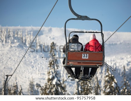 Ski lift carrying skiers - stock photo