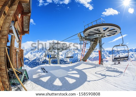 Ski lift chairs and sun on bright winter day  - stock photo