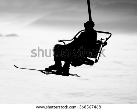Ski lift chairs on winter day over the clouds, cableway chair equipment sport skiing background /  silhouette of skier - stock photo