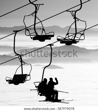 Ski lift chairs on winter day over the clouds, cableway funicular chair equipment sport skiing background /  silhouette of skiers on mountain hill  - stock photo