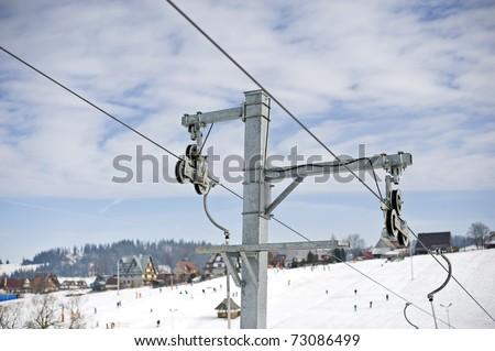Ski lift gears against a blue sky and ski resort. - stock photo