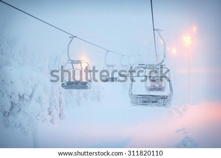 Ski lift in the fog. Ski resort in Ruka, Finland - stock photo