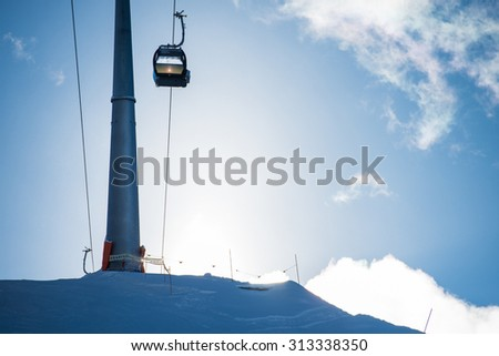 Ski lift or telecabine in a ski resort on a slope, covered with snow during wintersport season, with the sun rising over the mountain - stock photo